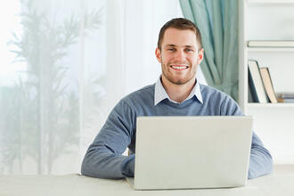 Happy smiling young businessman working in his home office-1