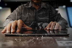businessman hand working on laptop computer with digital layer business strategy and social media diagram on wooden desk